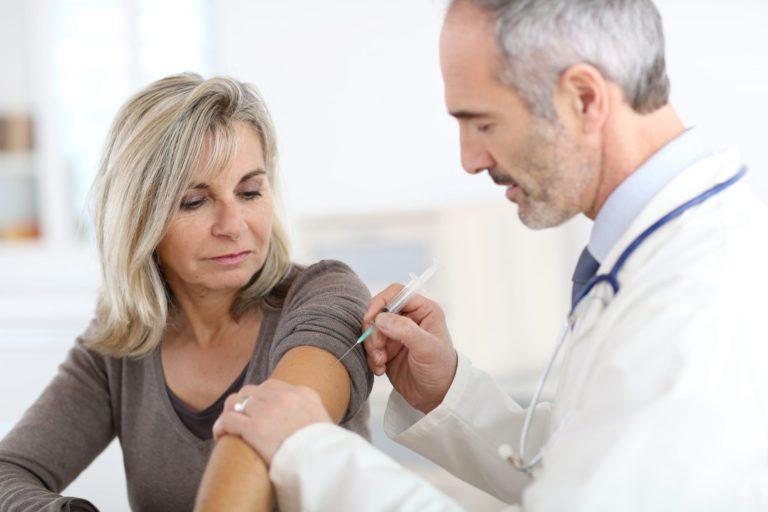 Mulher, maior de 60 anos, tomando vacinas