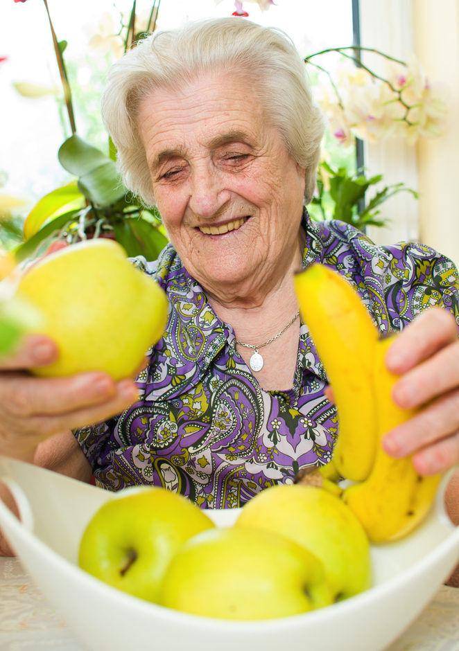 Idosa comendo alimentação saudável com frutas